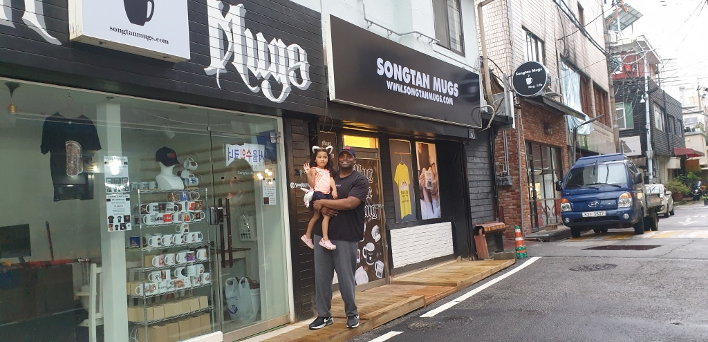 Jason and his daughter in front of Songtan Mugs retail shop